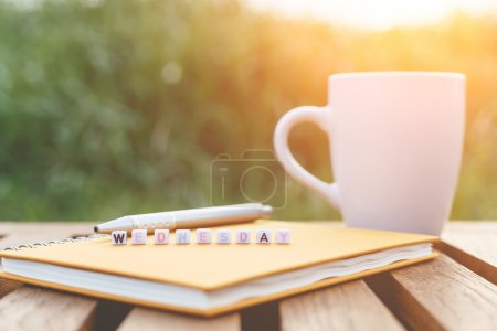 Wednesday written in letter beads and a coffee cup on table