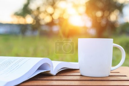 Photo for Coffee cup and book on the table in the morning - Royalty Free Image