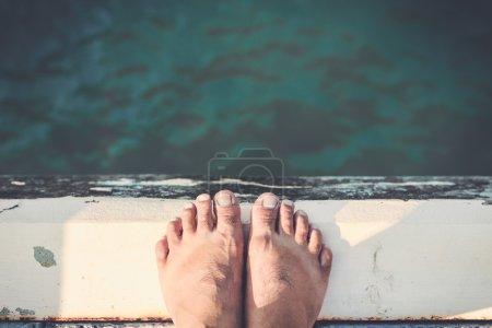 Foto de Pies descalzos, de pie en el borde de cemento cerca de mar - Imagen libre de derechos