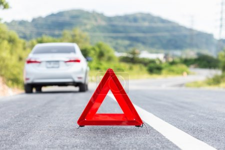 Photo for Red emergency stop sign and broken silver car on the road - Royalty Free Image
