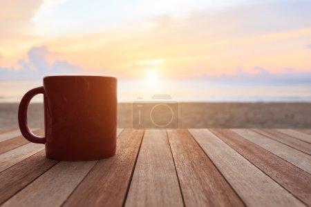 Photo pour Fermer tasse à café sur table en bois au coucher du soleil ou au lever du soleil plage - image libre de droit