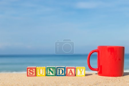 word SUNDAY in colorful alphabet blocks and coffee cup on tropic