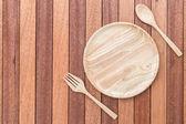 Prázdné dřevěné misky, vidlička a lžíce na dřevěný stůl