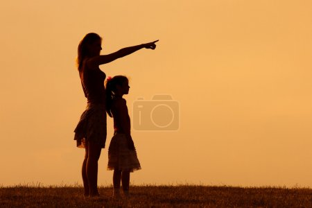 Mother and daughter in nature at sunset