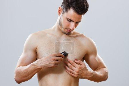 Handsome man shaving chest
