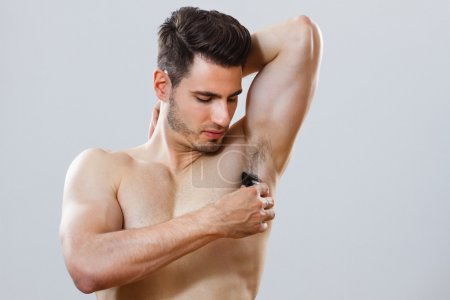 Handsome man shaving his armpit