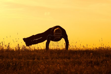 Photo for A silhouette of a woman practicing yoga,Yoga-Astavakra sana, Eight Angle Pose - Royalty Free Image