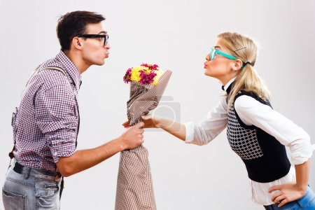 Young nerdy man is giving a bouquet of flowers to his nerdy lady