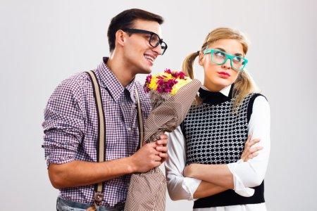 Photo pour Nerdy homme donne un bouquet de fleurs à sa petite amie, il avait fait une erreur et il espère qu'elle lui pardonnera, S'il vous plaît pardonnez-moi ma chère ! - image libre de droit