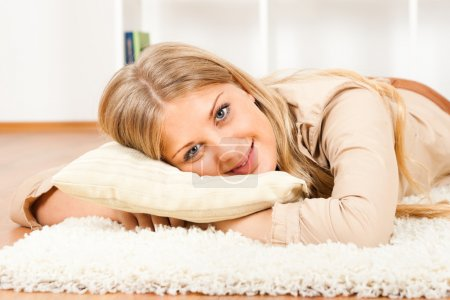 Photo for Smiling young woman lying on carpet and looking at camera,Relaxing time - Royalty Free Image