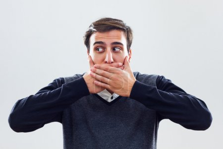 Young businessman covering mouth with hands