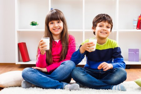 Photo for Cute little girl and little boy are holding glass of milk and looking at camera.We like to drink milk - Royalty Free Image