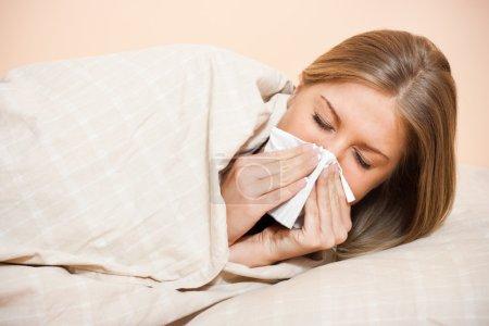 Photo pour Jeune femme soufflant dans les tissus, grippe - image libre de droit