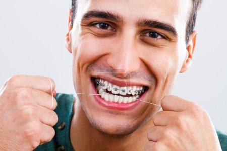 man using dental floss