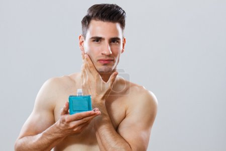 Portrait of handsome man holding aftershave