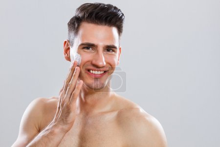 Handsome man applying shaving cream on his face