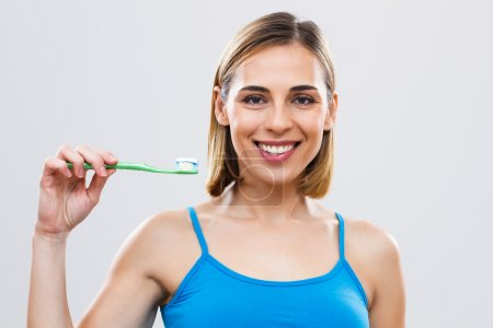 Beautiful woman holding toothbrush