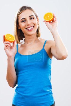 Woman is holding slices of orange