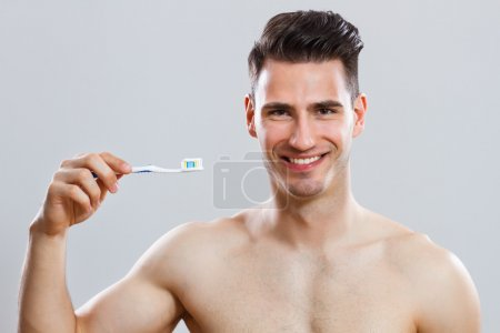Handsome man holding toothbrush