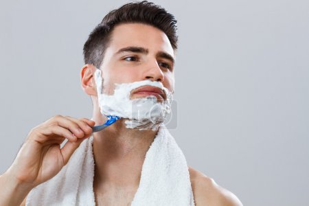 Photo of handsome man shaving his face