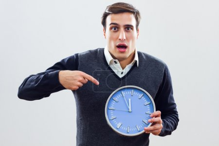 Frustrated businessman pointing at wall clock