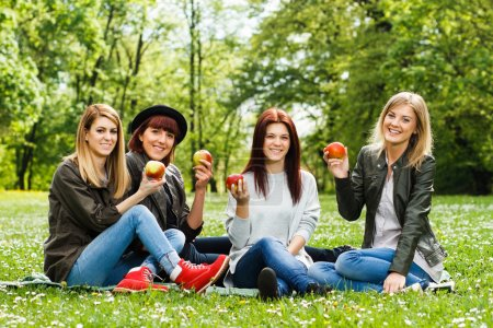 Photo for Young girls are sitting in the park and holding apple.Healthy snack for young girls - Royalty Free Image