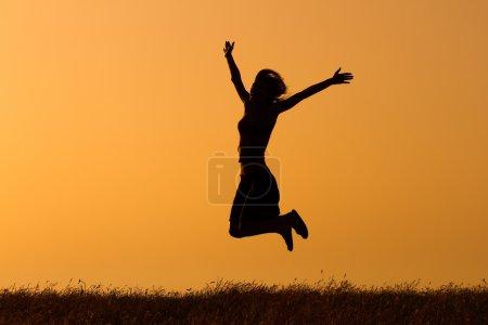 Photo pour Silhouette d'une femme sautant dans la nature. Femme heureuse - image libre de droit