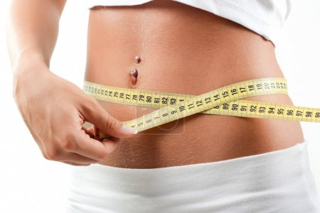 Young woman measuring belly after diet