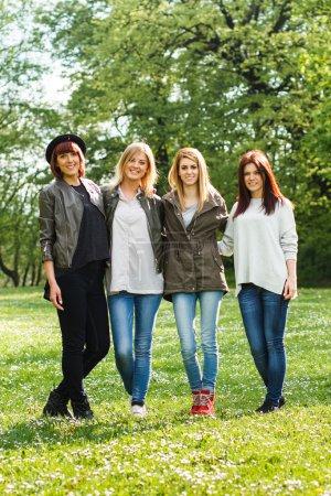 Photo pour Quatre jeunes filles debout dans le parc de printemps - image libre de droit