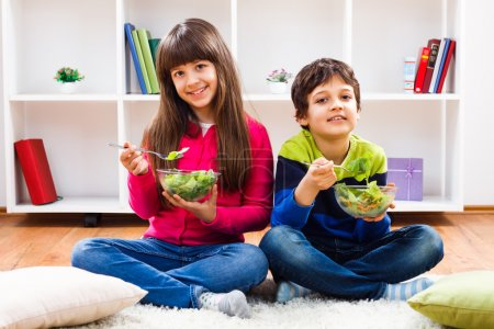 Photo for Boy and girl eating vegetables salad in room at home - Royalty Free Image