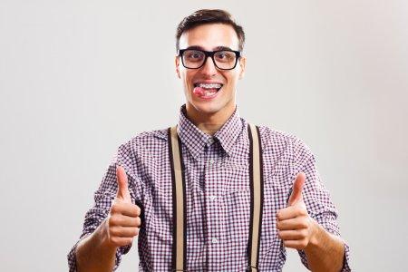 Photo pour Drôle jeune nerd homme portant bretelles montrant pouces jusqu'à isolé sur blanc - image libre de droit