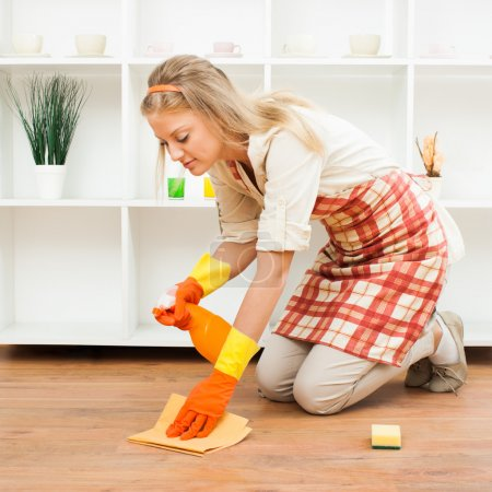 Photo for Young housewife is cleaning floor in room at home - Royalty Free Image