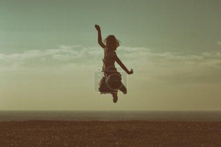 Photo pour Petite fille sautant et s'amuser dans la nature au coucher du soleil - image libre de droit
