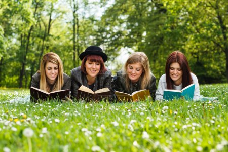 Four young girls reading books in park...