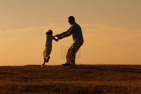 Photo for Happy father with girl having fun in nature at sunset - Royalty Free Image
