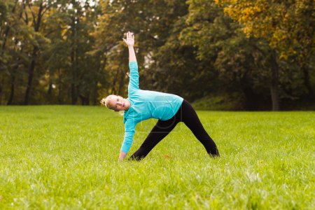 Woman practicing yoga in park
