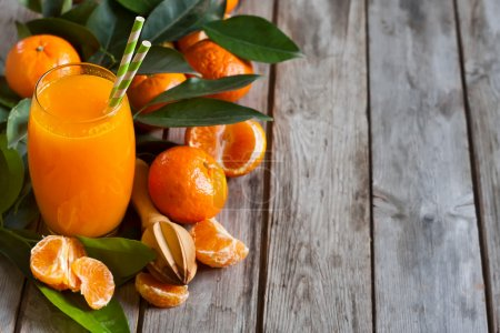 Photo for Glass of fresh tangerine juice with ripe tangerines, leaves and old-fashioned straws. Copy space background. - Royalty Free Image