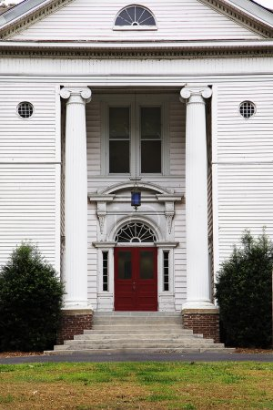 Old white historic home with columns and red door ...