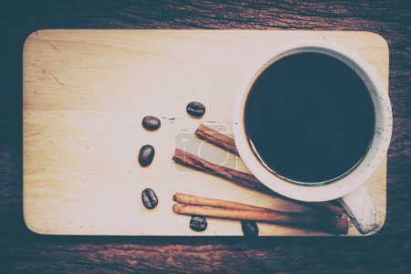 Coffee cup on the beans on wood.