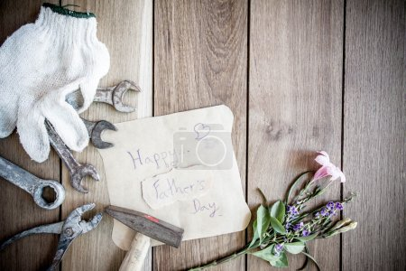 Happy Fathers Day with top border of tools and ties on a rustic