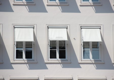Three windows on grey building with  white awnings and shadow