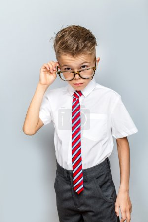 Studio portrait of male elementary pupil on light grey