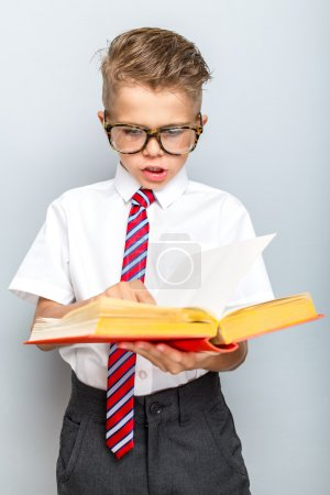 Photo for Back to school concept. Cheerful smiling little boy holding book on a grey background - Royalty Free Image