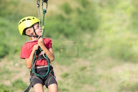 Photo pour Mignon petit garçon grimpant dans le parc d'aventure. mouvements, espace de copie - image libre de droit