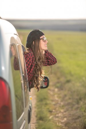 Photo for Freedom car travel concept - woman relaxing out of window in a car. Girl relaxing enjoying free holidays road trip - Royalty Free Image