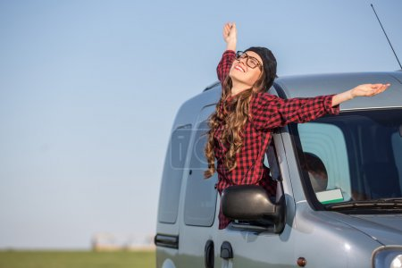 Photo for Freedom car travel concept - woman relaxing out of window in a car over blue sky. Girl relaxing enjoying free holidays road trip - Royalty Free Image