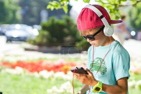 Stylish cute boy listening to music in city park