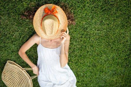Photo pour Gratuit femme jouir de la liberté de se sentir heureux en position couchée sur l'herbe avec un chapeau sur le visage, se concentrer sur le chapeau, copier espace, Découvre d'en haut - image libre de droit