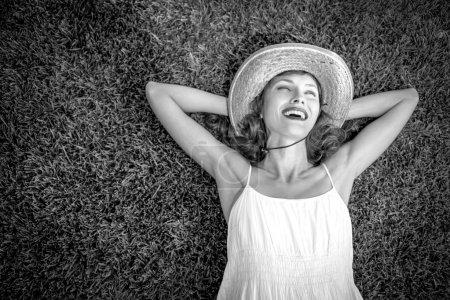 Photo pour Femme libre, jouir de la liberté de se sentir heureux en position couchée sur l'herbe. image noir et blanc, doux - image libre de droit