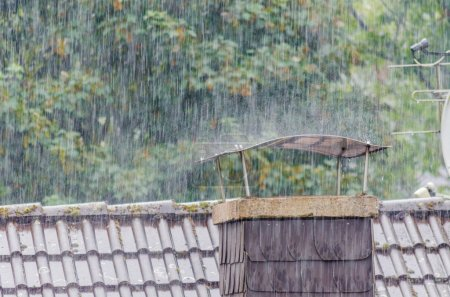 Photo pour Des gouttes de pluie, de fortes pluies, de la pluie sur le toit couvrent une cheminée . - image libre de droit